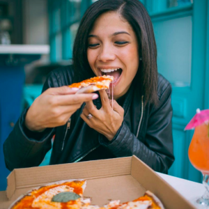 Lady eating pizza from box